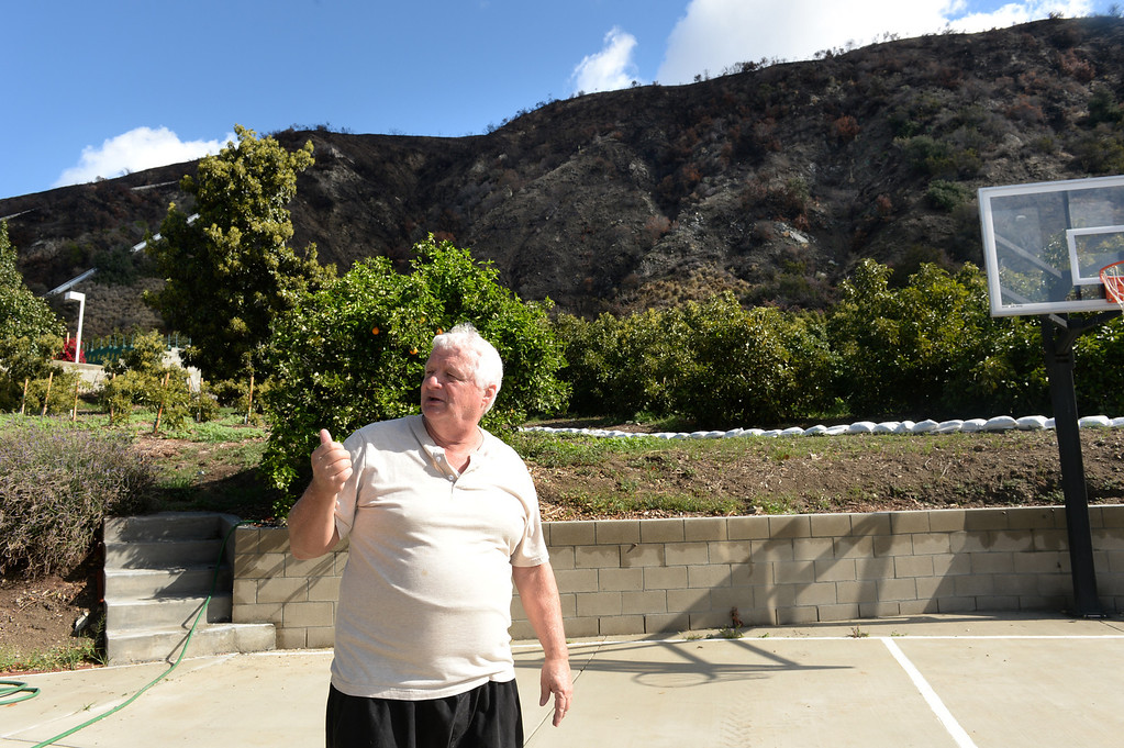 . Ed Heinlein shows the hills behind his home on Ridge View Drive in Azusa that threaten to flood the homes with the next storm on Thursday February 27, 2014. (Staff Photo by Keith Durflinger/San Gabriel Valley Tribune)
