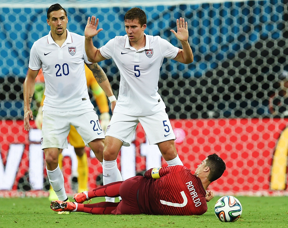 . Portugal\'s Cristiano Ronaldo begins to get up after going down while being challenged by United States\' Matt Besler, right, and United States\' Geoff Cameron, left, during the group G World Cup soccer match between the USA and Portugal at the Arena da Amazonia in Manaus, Brazil, Sunday, June 22, 2014. (AP Photo/Paulo Duarte)