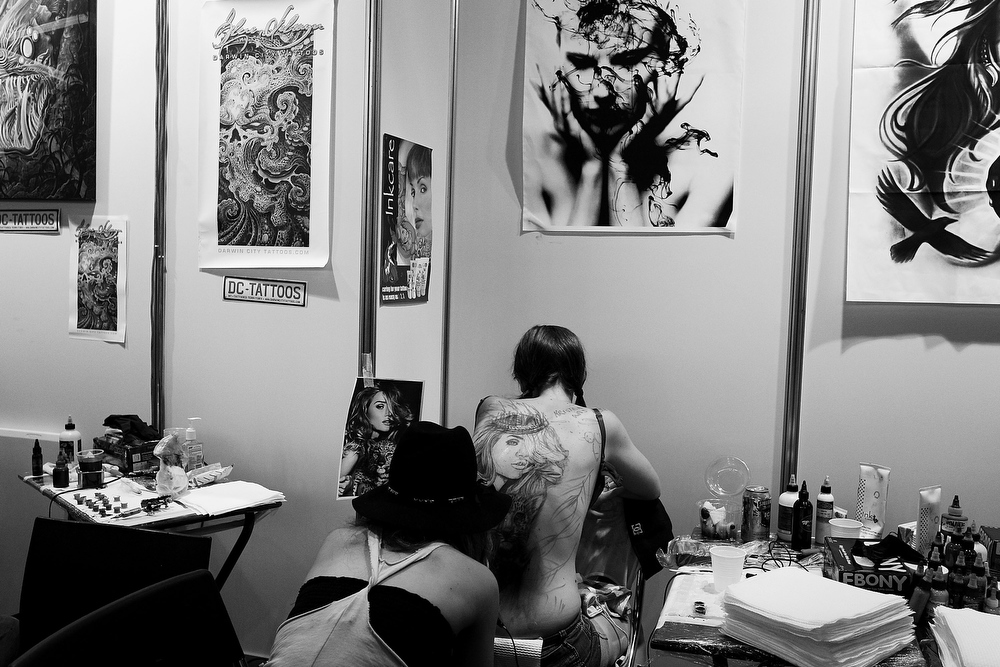 . Tattoo artist Kristen Sorrenson of \'Garage Ink\' works on a young woman\'s back during The Australian Tattoo & Body Art Expo at the Royal Hall of Industries, Moore Park on March 8, 2013 in Sydney, Australia. The annual three day event showcases some of Australia\'s best tattoo and body artists and is open to enthusiasts March 8-10.  (Photo by Lisa Maree Williams/Getty Images)