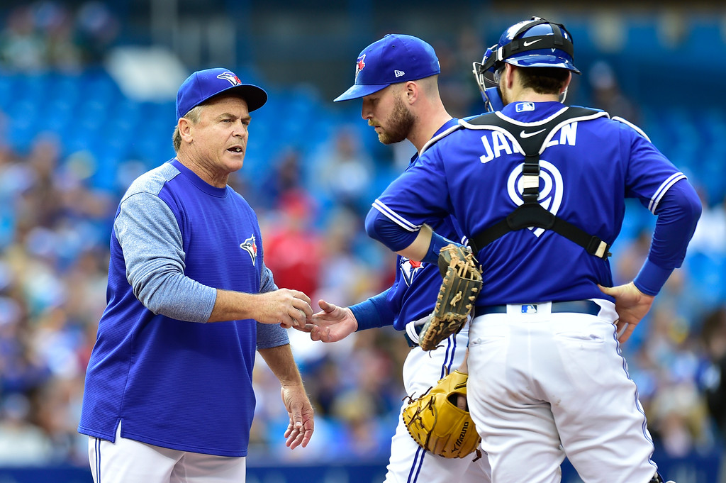 . Toronto Blue Jays manager John Gibbons, left, pulls starting pitcher Sean Reid-Foley (54) from the game as catcher Danny Jansen looks on during the fifth inning  of a baseball game against the Cleveland Indians in Toronto, Saturday, Sept .8, 2018. (Frank Gunn/The Canadian Press via AP)