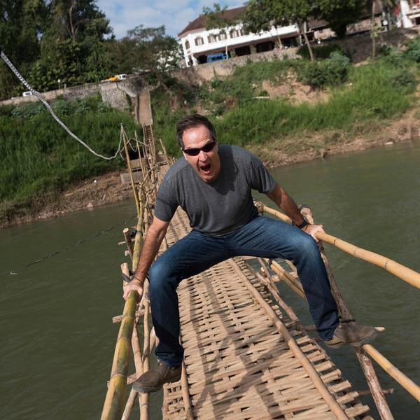 Portrait of man posing on bamboo bridge, Nam Khan river, Luang Prabang, Laos