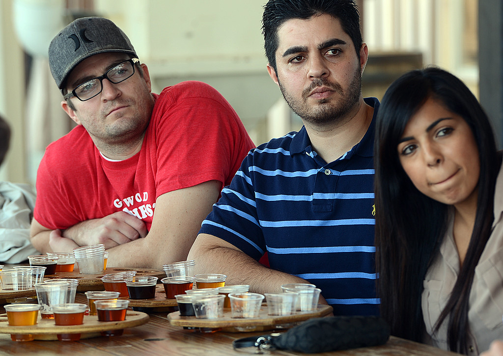 . Joel Sheffer, 28, of Redlands, from the left, Navied Jabbari, 26, of San Jose and Brittany Jimenez, 25, of Mentone listen to a press conference at Hanger 24 Brewery, Tuesday December 17, 2013, where officials anounce Responsible Redlands. Local restaurants and businesses, like Hanger 24 Brewery and Redlands Cab Company, are teaming up with the City of Redlands, Redlands police department and the San Bernardino County District Attorney\'s office to help curb drunk driving in Redlands. From December 21, 2013 through January 1, 2014 Responsible Redlands will provide free rides home from local Redlands bar businesses, up to four miles. (Photo by Rick Sforza/Redlands Daily Facts)