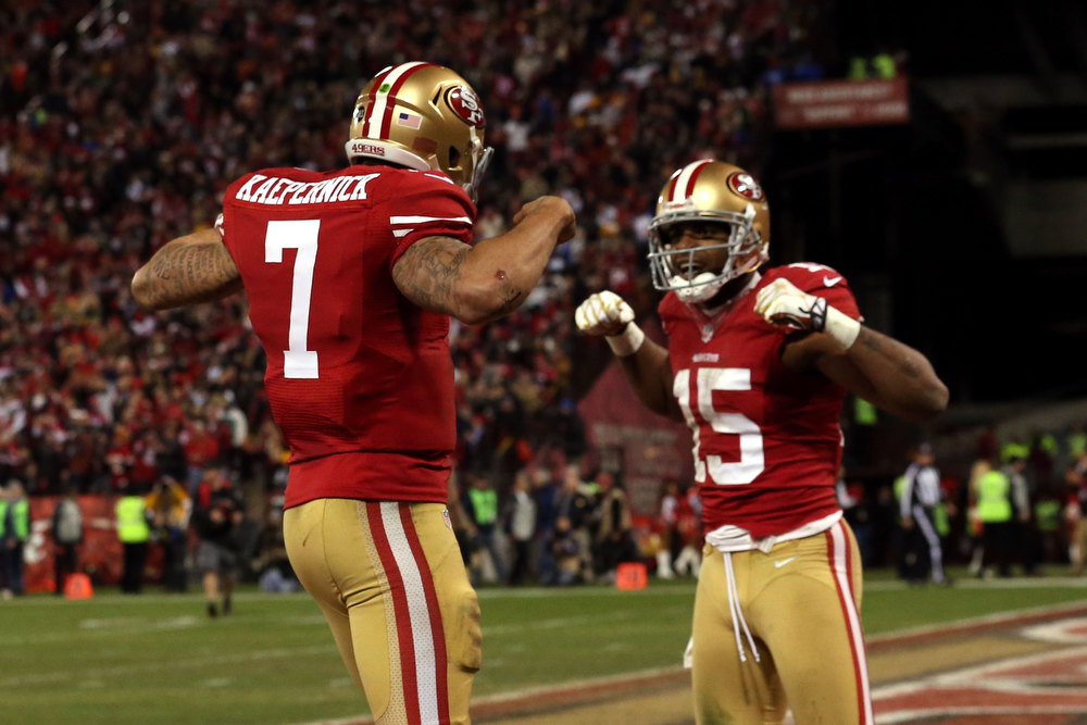 Description of . Quarterback Colin Kaepernick #7 of the San Francisco 49ers celebrates with wide receiver Michael Crabtree #15 after running the ball for a touchdown against the Green Bay Packers in the third quarter during the NFC Divisional Playoff Game at Candlestick Park on January 12, 2013 in San Francisco, California.  (Photo by Stephen Dunn/Getty Images)