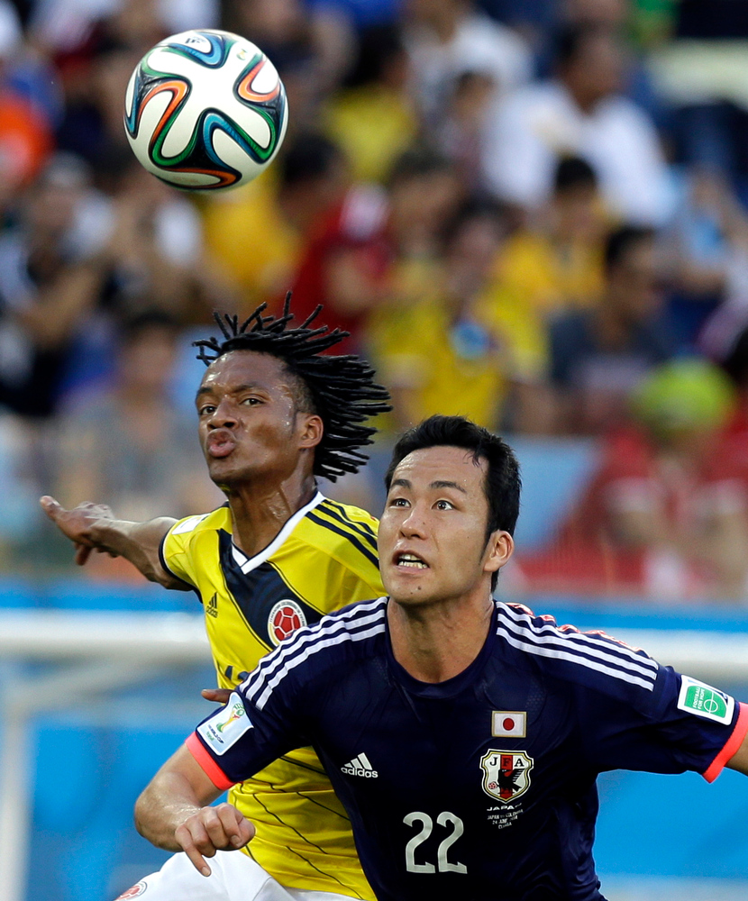 . Colombia\'s Juan Cuadrado, left, and Japan\'s Maya Yoshida battle for the ball during the group C World Cup soccer match between Japan and Colombia at the Arena Pantanal in Cuiaba, Brazil, Tuesday, June 24, 2014. (AP Photo/Thanassis Stavrakis)