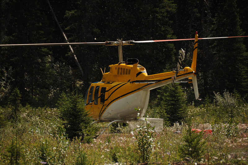 After dropping off three passengers, the helicopter pilot connected a cable to the undercarriage and headed up.