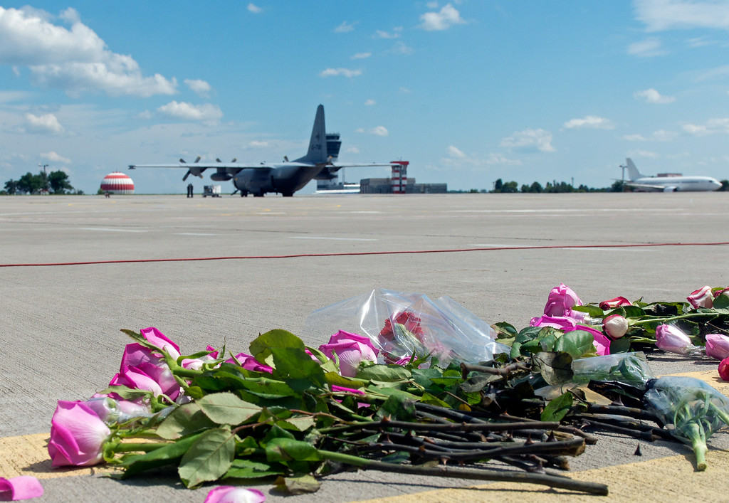 . Flowers lay on the tarmac as a ground Hercules transport aircraft of the Royal Dutch Airforce, carrying bodies from downed Malaysia Airlines flight MH17, prepares to take off from Kharkiv airport on July 23, 2014. The first plane carrying bodies from downed Malaysia Airlines flight MH17 on July 23 left eastern Ukraine for the Netherlands. The Dutch military aircraft took off from the airport in the government-controlled city of Kharkiv bound for Eindhoven after the first group of victims\' remains were loaded onto the plane in wooden coffins.  AFP PHOTO/ SERGEY  BOBOK/AFP/Getty Images