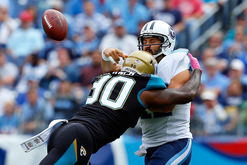 . Charlie Whitehurst #12 of the Tennessee Titans is hit by Andre Branch #90 of the Jacksonville Jaguars during the second quarter of a game at LP Field on October 12, 2014 in Nashville, Tennessee.  (Photo by Wesley Hitt/Getty Images)