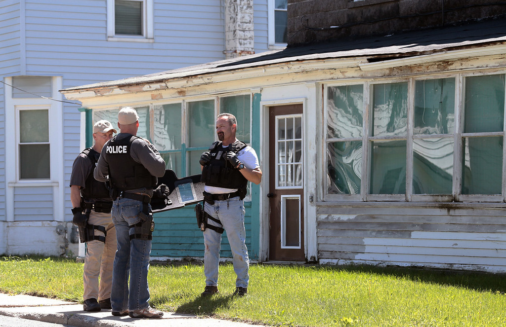 . Law enforcement officers sweep through Smith Street in Dannemora, N.Y. on Saturday, June 6, 2015 looking for signs of the escaped convicts. Two convicted murderers used power tools to cut through steel pipes at a maximum-security prison near the Canadian border and escape through a manhole, Gov. Andrew Cuomo said Saturday. (Gabe Dickens/Press-Republican via AP)