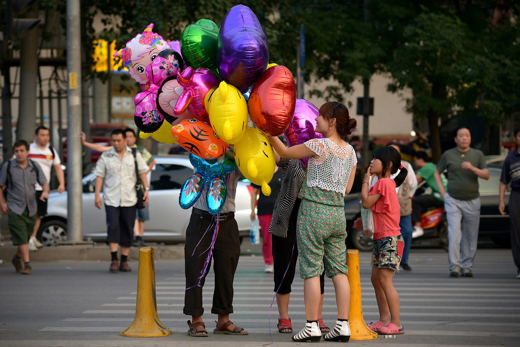 . A girl prepares to buy a balloon along a street outside a park in Beijing on June 1, 2013 . Tens of thousands of children celebrate the International Children\'s Day in China. WANG ZHAO/AFP/Getty Images