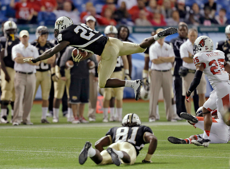 . Central Florida running back Latavius Murray (28) is sent flying on a hit by Ball State safety Chris Pauling (25) during the first quarter of the Beef \'O\' Brady\'s Bowl NCAA college football game Friday, Dec. 21, 2012, in St Petersburg, Fla. (AP Photo/Chris O\'Meara)