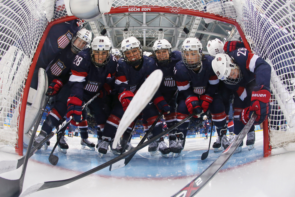 . Members of Team USA pack into the opening of the net for a photograph before the first period of the 2014 Winter Olympics women\'s semifinal ice hockey game against Sweden at Shayba Arena, Monday, Feb. 17, 2014, in Sochi, Russia. (AP Photo/Bruce Bennett, Pool)