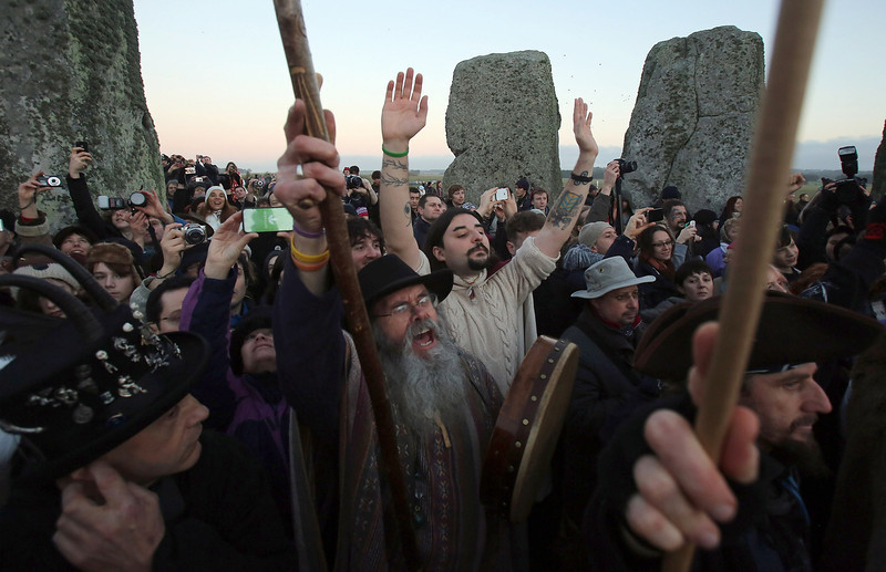 . People cheers as the sun rises as druids, pagans and revellers celebrate the winter solstice at Stonehenge on December 21, 2012 in Wiltshire, England. Predictions that the world will end today as it marks the end of a 5,125-year-long cycle in the ancient Maya calendar, encouraged a larger than normal crowd to gather at the famous historic stone circle to celebrate the sunrise closest to the Winter Solstice, the shortest day of the year.  (Photo by Matt Cardy/Getty Images)