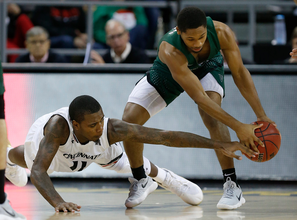 . Cleveland State guard Kasheem Thomas, right, grabs a loose ball in front of Cincinnati forward Gary Clark (11) during the second half of an NCAA college basketball game Thursday, Dec. 21, 2017, in Highland Heights, Ky. Cincinnati won 81-62. (AP Photo/Gary Landers)