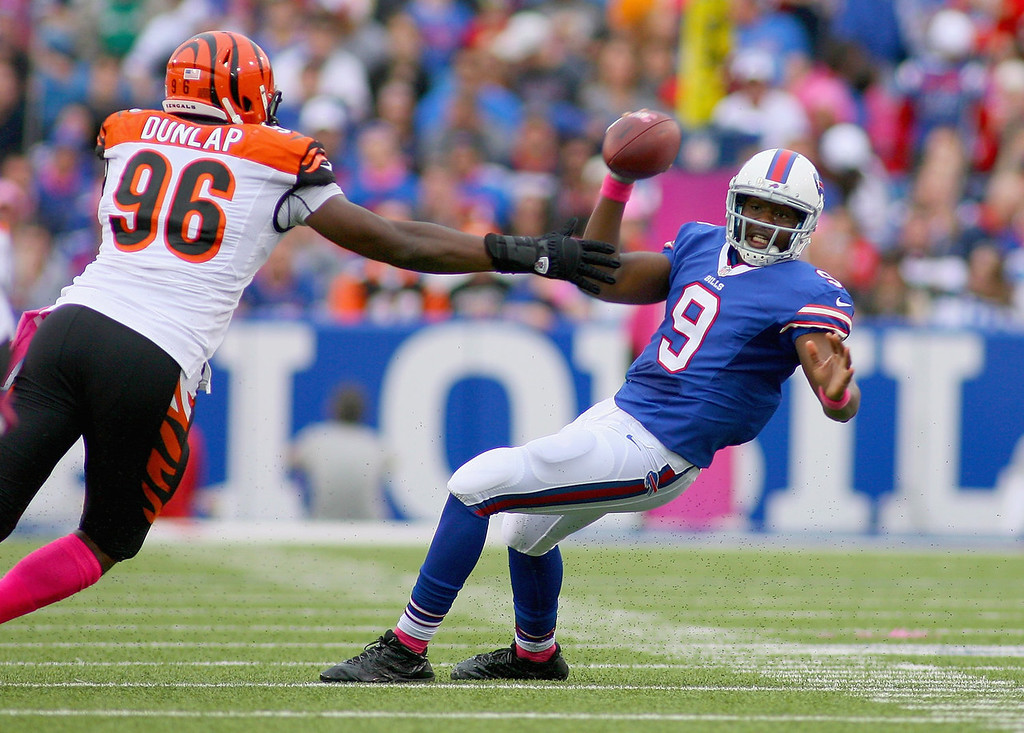 . Thad Lewis #9 of the Buffalo Bills avoids a sack by  Carlos Dunlap #96 of the Cincinnati Bengals at Ralph Wilson Stadium on October 13, 2013 in Orchard Park, New York.  (Photo by Rick Stewart/Getty Images)