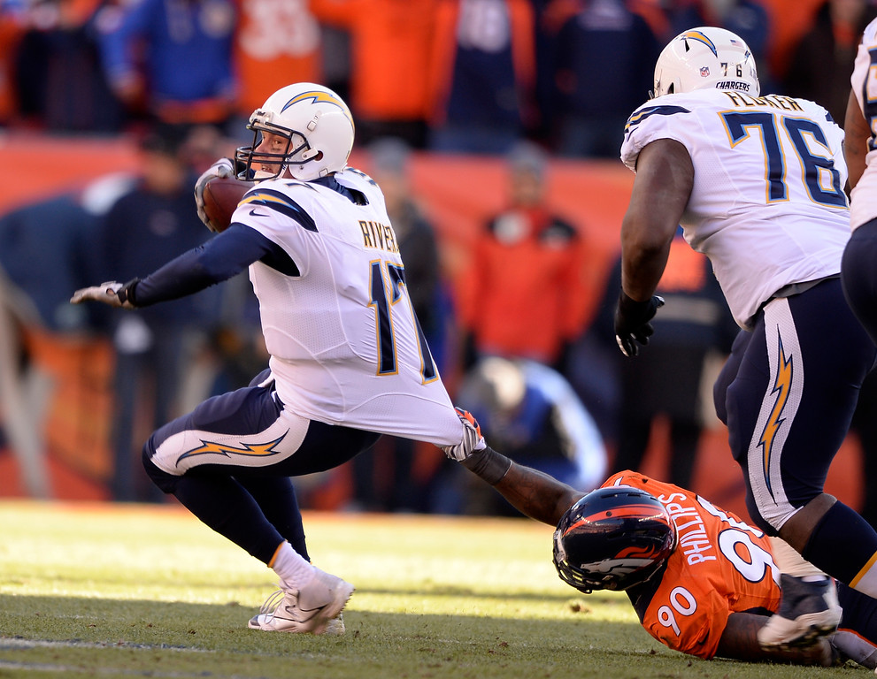 . DENVER, CO - JANUARY 12: Denver Broncos defensive end Shaun Phillips (90) pulls down San Diego Chargers quarterback Philip Rivers (17) for a first quarter sack. The Denver Broncos vs. The San Diego Chargers in an AFC Divisional Playoff game at Sports Authority Field at Mile High in Denver on January 12, 2014. (Photo by John Leyba/The Denver Post)