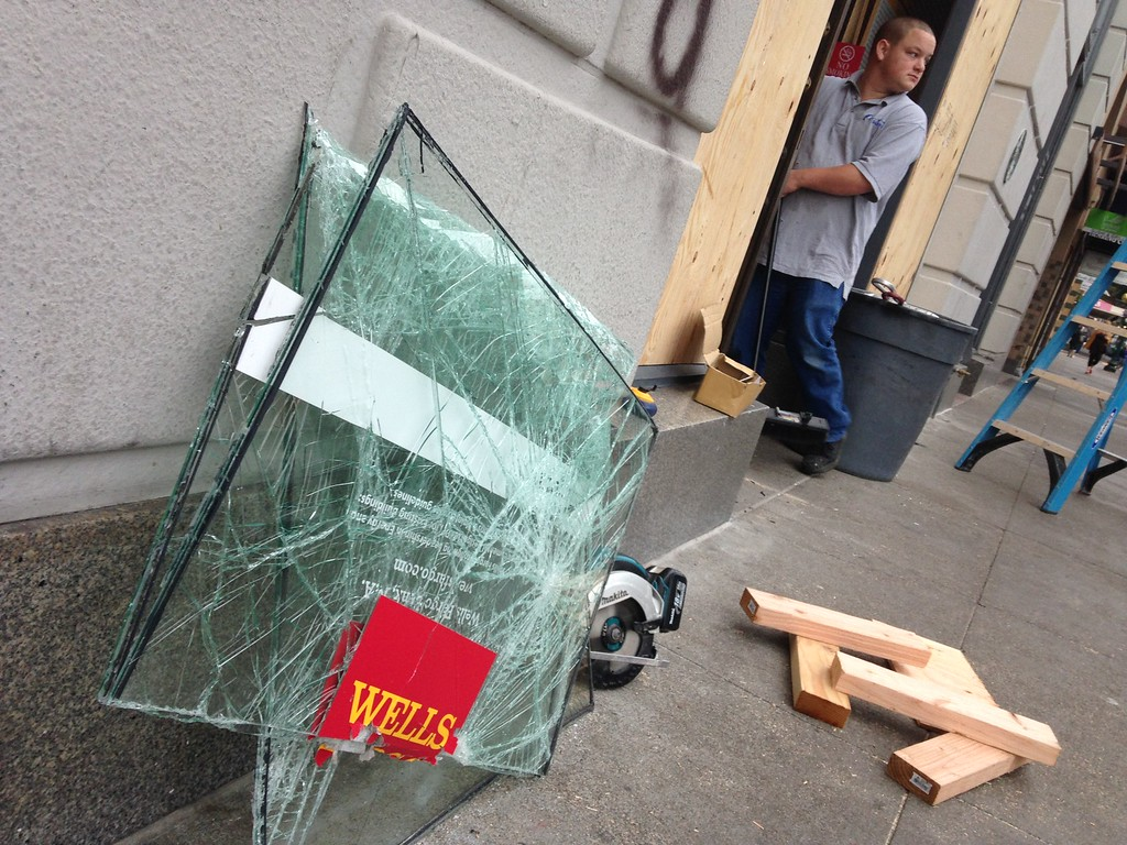 . Workers board up broken windows at the Wells Fargo on Shattuck Avenue and Center Street in Berkeley, Calif., on Monday, Dec. 8, 2014, in the aftermath of the Sunday night protest. (Laura A. Oda/Bay Area News Group)