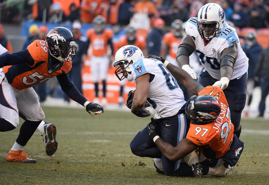 . Denver Broncos defensive end Malik Jackson (97) tackles Tennessee Titans tight end Visanthe Shiancoe (80) in the second quarter.  (Photo by John Leyba/The Denver Post)