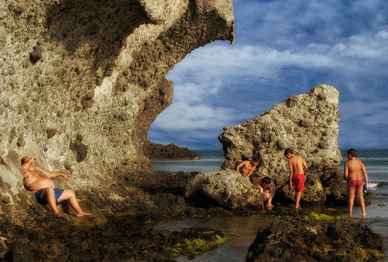 Grandfather keeps an eye on the kids.  Cabo de Gata nature reserve, Almeria, Spain