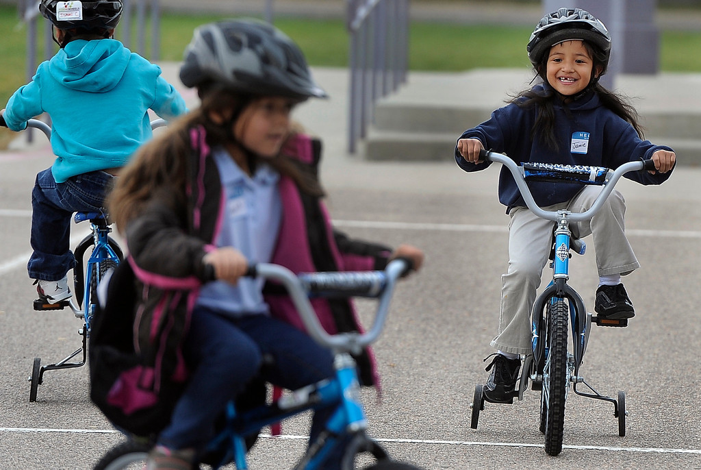 . DENVER, CO - Oct. 11: Jamie Correa, 6, right, joins her classmates for a spin on the school blacktop. Wish for Wheels and its volunteers build and give away over one hundred bikes to kindergarteners and first-graders at Smith Renaissance School in Park Hill. Wish for Wheels says its goal with one-in-five children liven in poverty, is to give as many kids as possible their first brand new bike and helmet. (Photo By Kathryn Scott Osler/The Denver Post)