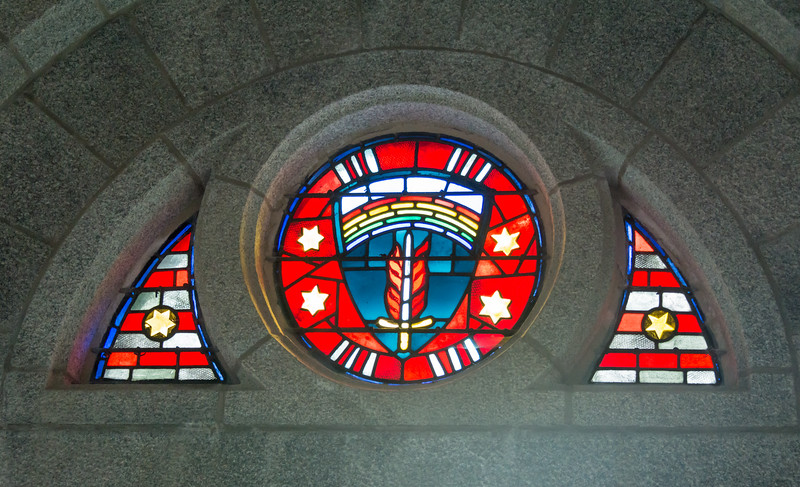 Memorall Chapel, over entrance:  emblem of the Supreme Headquarters Allied Expeditionary Force.  The cemetery is laid out along this sword-and shield motif, with the mall as a blade and headstones arching out as flames.