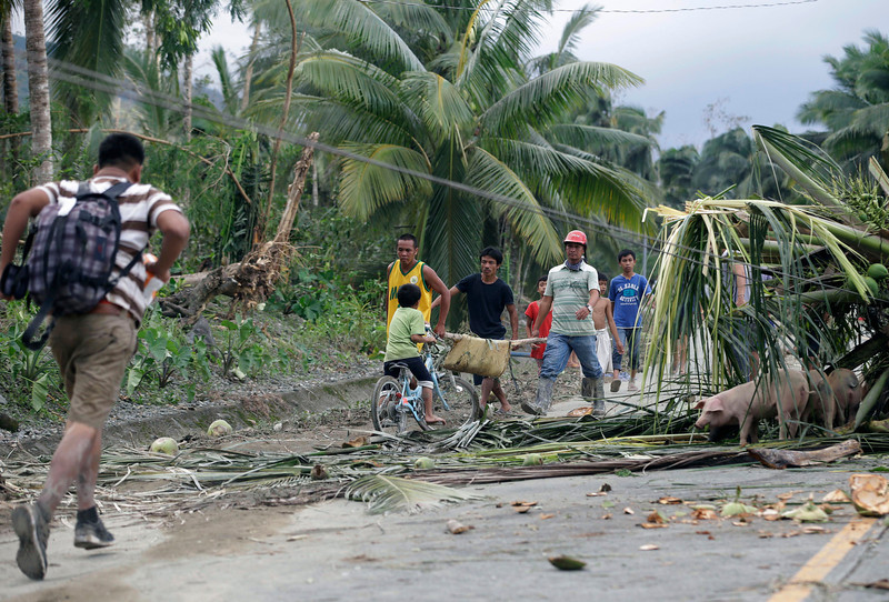 . Residents carry the body of a flash-flood victim in the village of Andap, New Bataan township, Compostela Valley in southern Philippines Wednesday, Dec. 5, 2012. Typhoon Bopha, one of the strongest typhoons to hit the Philippines this year, barreled across the country\'s south on Tuesday, killing scores of people while triggering landslides, flooding and cutting off power in two entire provinces. (AP Photo/Bullit Marquez)