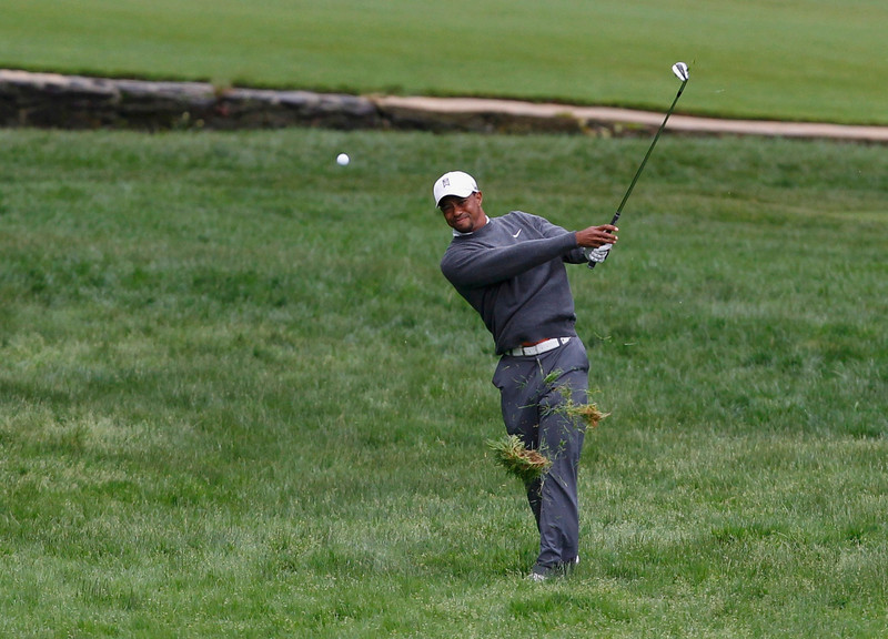 . Tiger Woods of the U.S. makes his second shot on the 12th hole during the weather delayed first round of the 2013 U.S. Open golf championship at the Merion Golf Club in Ardmore, Pennsylvania, June 14, 2013.  REUTERS/Matt Sullivan