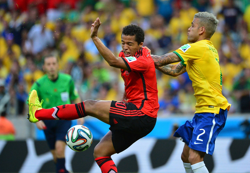 . Mexico\'s forward Giovani Dos Santos (L) vies with Brazil\'s defender Dani Alves (R) during a Group A football match between Brazil and Mexico in the Castelao Stadium in Fortaleza during the 2014 FIFA World Cup on June 17, 2014.  (YURI CORTEZ/AFP/Getty Images)