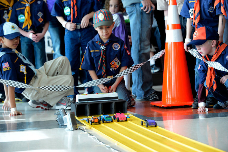 . COMMERCE CITY, CO. - JANUARY 26: Scouts watch the  cars cross the finish line during the 2013 Pack 414 Pinewood Derby races at Ortho Stuart Middle School January 26, 2013 in Commerce City. The pinewood cars weigh 5 oz and are 7 inches long. The cars take about 3 second to go down the track.  The scouts can either buy a kit with the car already shaped or buy a block of wood and carve their own.  (Photo By John Leyba / The Denver Post)