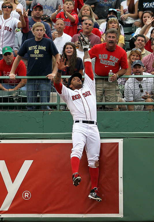 . Darnell McDonald #54 of the Boston Red Sox leaps to make a catch from a ball hit by Kelly Johnson #2 of the Toronto Blue Jays in the ninth inning at Fenway Park June 27, 2012  in Boston, Massachusetts.  (Photo by Jim Rogash/Getty Images)