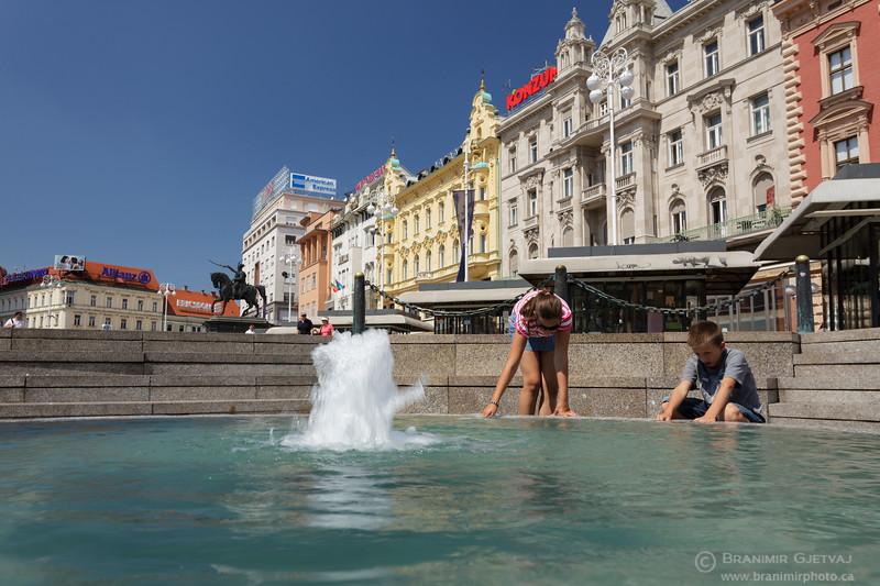 Children play around Manduševac water fountain on Jelačić Square in Zagreb, Croatia