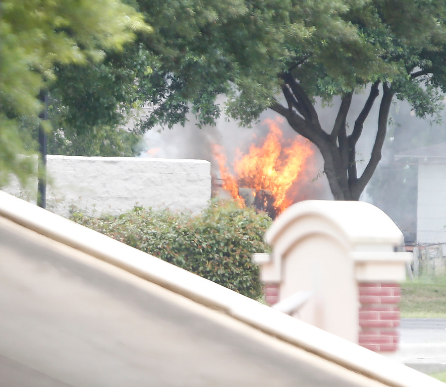 . The armored van used by a lone shooter to attack and then flee Dallas Police Headquarters catches fire outside a fast food restaurant on June 13, 2015 in Hutchins, Texas. Authorities used controlled charges to discharge pipe bombs in the van after the shooter reportedly unleashed multiple rounds and planted explosive devices around the station before leading police on a chase that ended in a standoff in the parking lot of a fast food resturant. (Photo by Stewart F. House/Getty Images)
