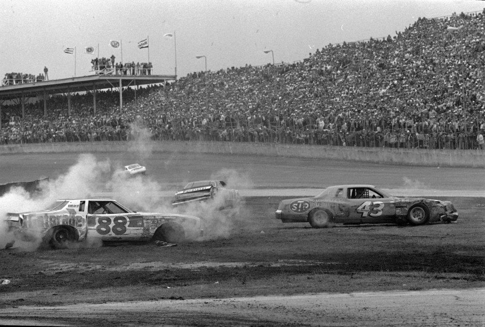Description of . Darrell Waltrip's car (88) sits smoking and crumpled off the track,  along with David Pearson (21) after a three-car crash at the Daytona Speedway during the Daytona 500 race, Feb. 19, 1978.  (AP Photo/Jim Kerlin)