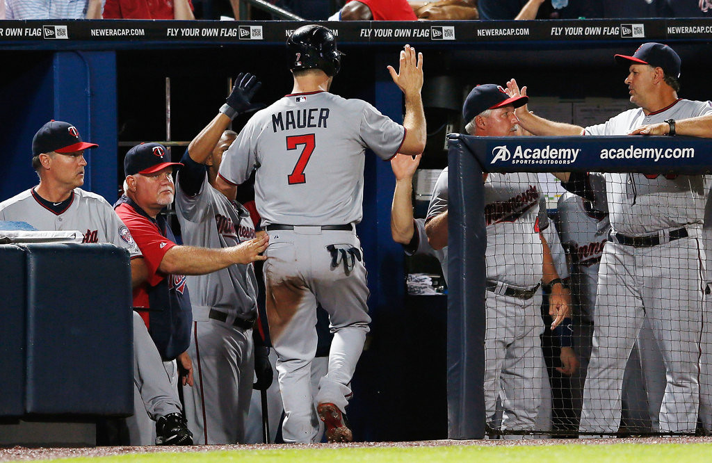 . Joe Mauer of the Minnesota Twins celebrates in the dugout after scoring in the third inning.  (Photo by Kevin C. Cox/Getty Images)