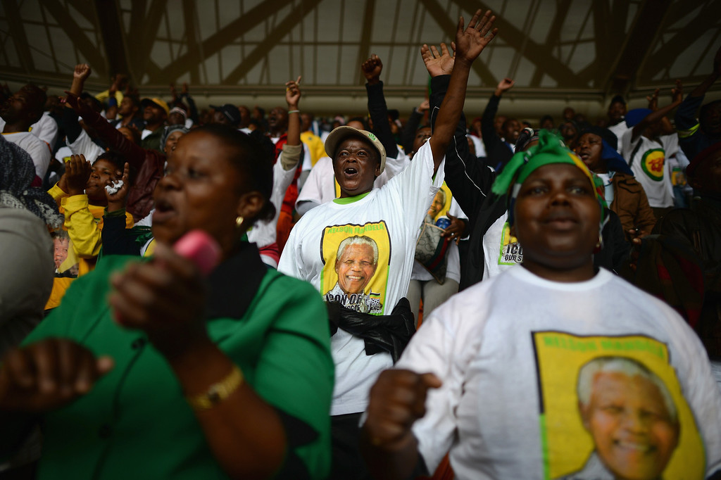 . JOHANNESBURG, SOUTH AFRICA - DECEMBER 10:  Members of the public attend the Nelson Mandela memorial service at the FNB Stadium, on December 10, 2013 in Johannesburg, South Africa. Over 60 heads of state have travelled to South Africa to attend a week of events commemorating the life of former South African President Nelson Mandela. Mr. Mandela passed away on the evening of December 5, 2013 at his home in Houghton at the age of 95. Mandela became South Africa\'s first black president in 1994 after spending 27 years in jail for his activism against apartheid in a racially-divided South Africa.  (Photo by Jeff J Mitchell/Getty Images)