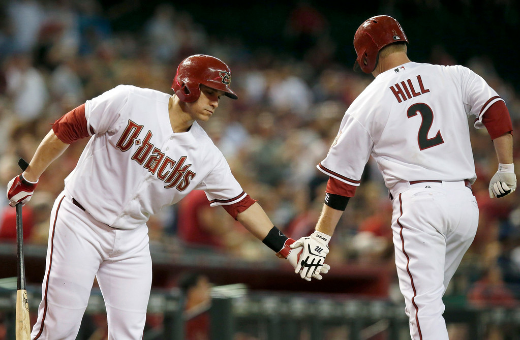 . Arizona Diamondbacks\' Aaron Hill (2) celebrates his home run against the Detroit Tigers with teammate Miguel Montero, left, during the first inning of a baseball game on Tuesday, July 22, 2014, in Phoenix. (AP Photo)
