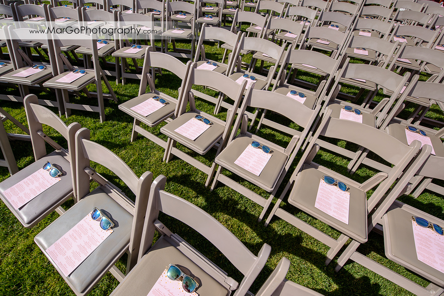 sunglasess on the guests' chairs at wedding ceremony site at Palm Event Center in the Vineyard in Pleasanton