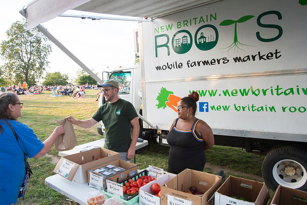 08/05/19 Wesley Bunnell | Staff Nic Tedesco, L, and Jasiry Valentin assist a customer at the New Britain Roots mobile farmers market truck on Monday evening during a concert at Walnut Hill Park.