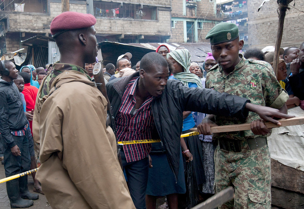 . Kenyan Paramilitary soldiers stop a citizen from crossing the police line at the site of a building collapse in Nairobi, Kenya, Saturday, April 30, 2016. A six-story residential building in a low income area of the Kenyan capital collapsed Friday under heavy rain and flooding, trapping a number of people in the rubble, Kenyan officials said.(AP Photo/Sayyid Abdul Azim)