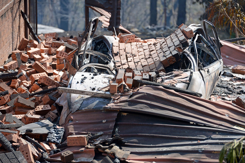 . A car lies under bricks at the front of a house destroyed by bush fires at Winmalee in Sydney\'s Blue Mountains on October 18, 2013. AFP PHOTO / Greg WOOD/AFP/Getty Images