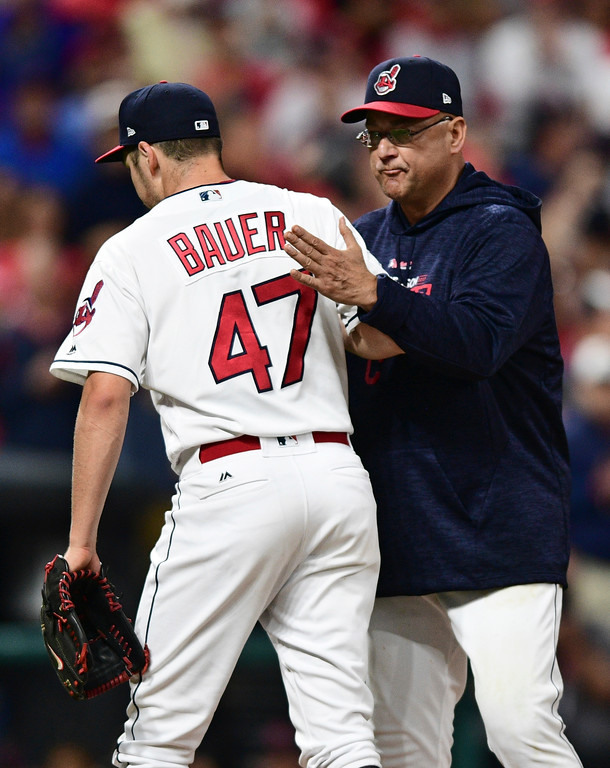 . Cleveland Indians manager Terry Francona congratulates starting pitcher Trevor Bauer as Bauer leaves during the seventh inning against the New York Yankees in Game 1 of a baseball American League Division Series, Thursday, Oct. 5, 2017, in Cleveland. Bauer pitched 6 2/3 innings and gave up two hits. (AP Photo/David Dermer)