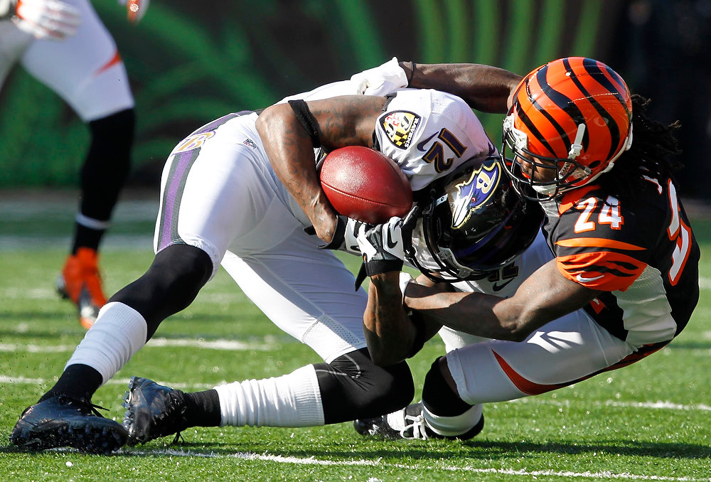 Description of . Baltimore Ravens\' Jacody Jones (12) is tackled by Cincinnati Bengals\' Adam Jones (24) during the first half of play in their NFL football game at Paul Brown Stadium in Cincinnati, Ohio, December 30, 2012.      REUTERS/John Sommers II