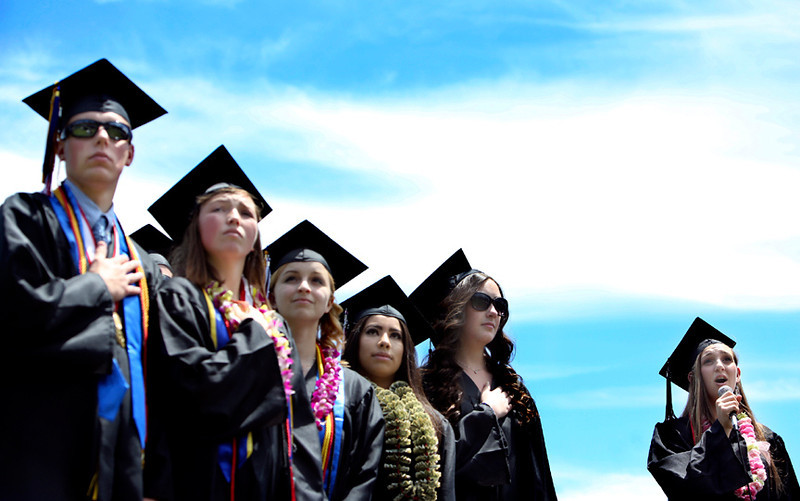 . San Lorenzo Valley High graduates stand for the singing of the National Anthem during the school\'s 2013 graduation ceremony in Felton on Friday. (Kevin Johnson/Sentinel)