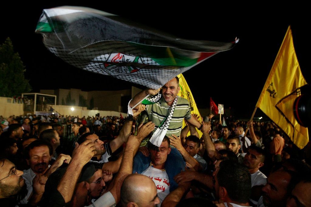 . A released Palestinian prisoner Esmat Mansour, center, waves a flag as he is cheered at the Palestinian Authority headquarters in the West Bank city of Ramallah, Wednesday, Aug. 14 , 2013. Israel released 26 Palestinian inmates, including many convicted in grisly killings, on the eve of long-stalled Mideast peace talks, angering families of those slain by the prisoners, who were welcomed as heroes in the West Bank and Gaza. (AP Photo/Majdi Mohammed)