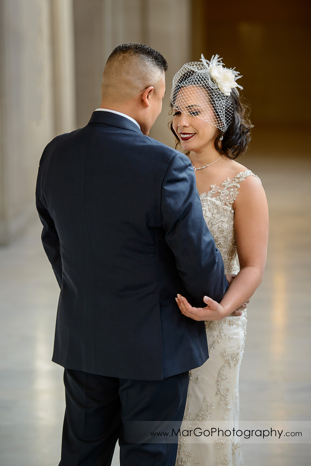 bride and groom hugging during first look at San Francisco City Hall