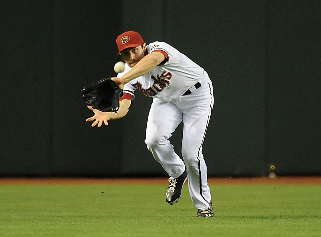 . PHOENIX, AZ - APRIL 25:  AJ Pollock #11 of the Arizona Diamondbacks makes a play on a fly ball against the Colorado Rockies at Chase Field on April 25, 2013 in Phoenix, Arizona.  (Photo by Norm Hall/Getty Images)