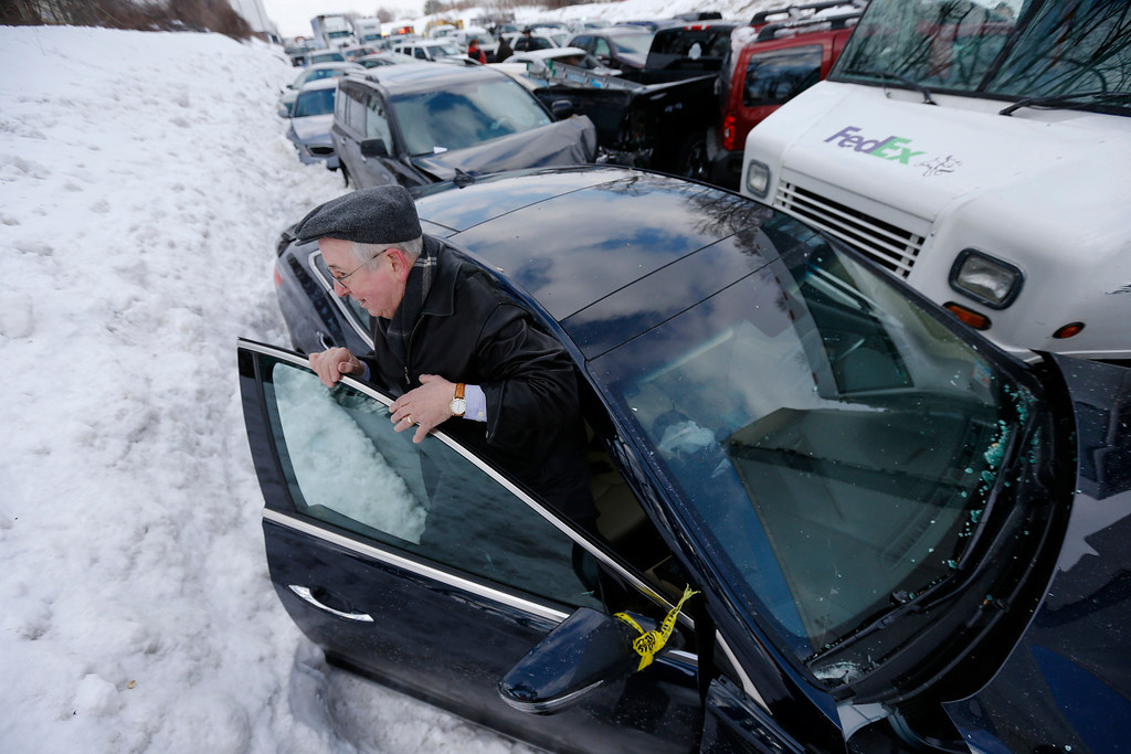 . Jerry Troy squeezes out of his vehicles that is piled up in an accident, Friday, Feb. 14, 2014, in Bensalem, Pa. Traffic accidents involving multiple tractor trailers and dozens of cars have completely blocked one side of the Pennsylvania Turnpike outside Philadelphia and caused some injuries. (AP Photo/Matt Rourke)