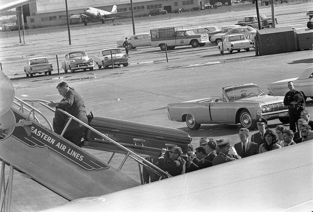 """. President Kennedy\'s casket is loaded onto Air Force One at Love Field in Dallas. Onlookers include Lawrence \""""Larry\"""" O\'Brien, Jacqueline Kennedy and Dave Powers. Cecil Stoughton/John F. Kennedy Presidential Library and Museum"""