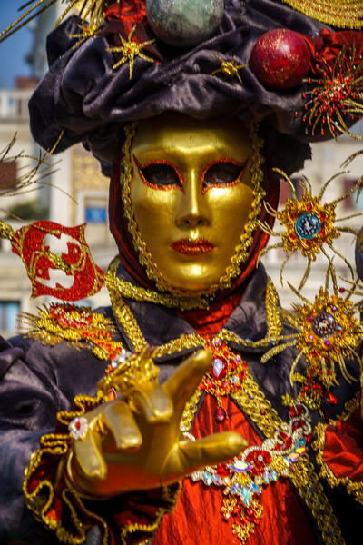 Stunning & colorful Venice carnival costume shot at Saint Mark's Square (Piazza San Marco). One can also recognize the well known Clock Tower in the nice blurred background.