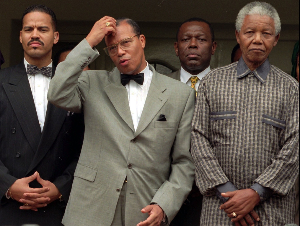 . Leader of Nation of Islam, Louis Farrakhan, center, addresses the media, Sunday January 28, 1996 after a short meeting with South African President Nelson Mandela, right, at the president\'s Johannesburg home. During a brief press conference after the meeting Mandela told Farakhan that South Africa rejects racism, sexism and reveres all religions. Farakhan\'s son, Mustafa (far left), man in rear is an unidentified Farakhan aid.(AP Photo/Joao Silva)