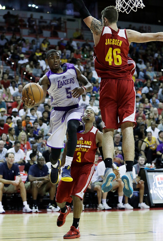 . Los Angeles Lakers\' Xavier Munford passes around Cleveland Cavaliers\' Eric Jacobsen during the first half of an NBA summer league basketball game, Thursday, July 14, 2016, in Las Vegas. (AP Photo/John Locher)